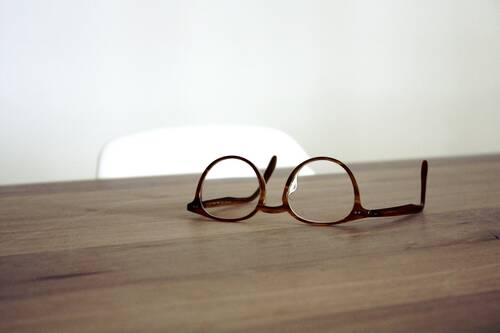 A pair of glasses on a wooden surface - CHROSI OPTIK Gutschein-Shop